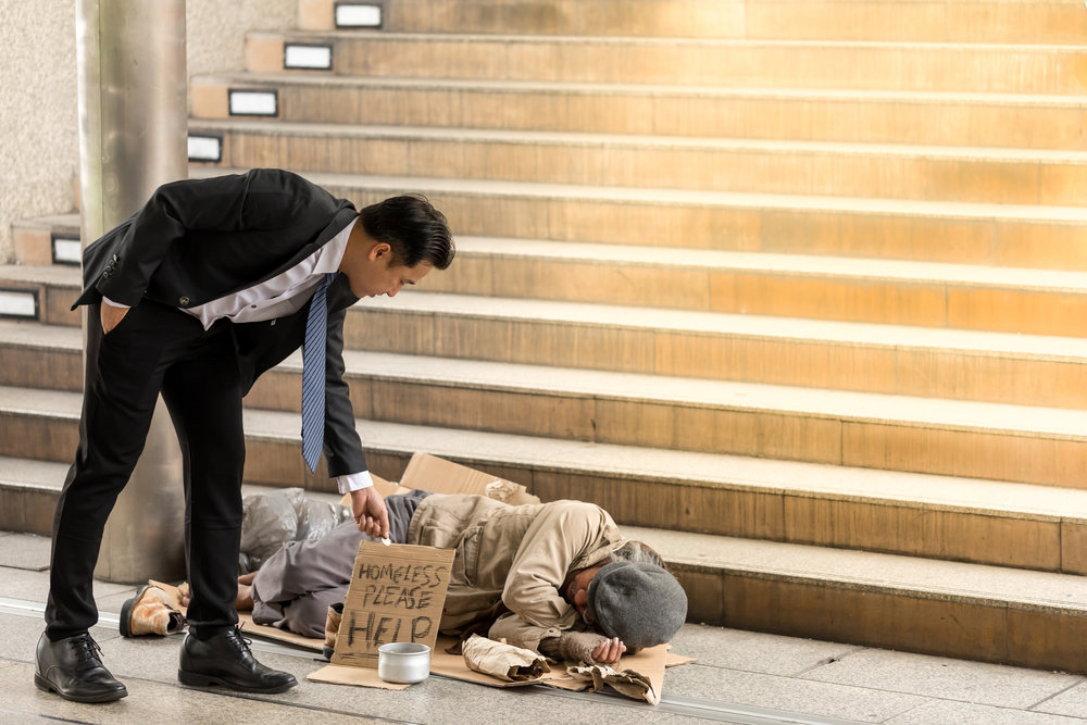 Portrait image of Businessmen's holding money gives money to a mature homeless man is Sleeping. Senior person hands begging for money